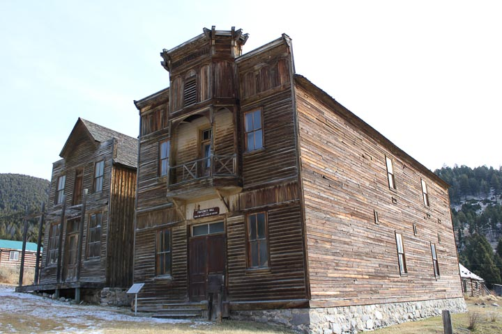 Two two-story wooden buildings, with snowy hills on the edge