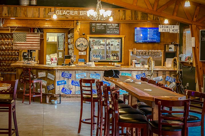 """Long table surrounded by chairs in front of a bar; hanging American flag, open door, beer taps, and TV screen behind the bar, and hanging sign that says """"Growler Fills Here"""""""