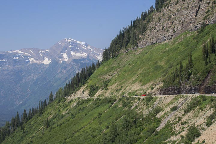 Red car driving on a grassy hillside with glaciers on a mountain in the background
