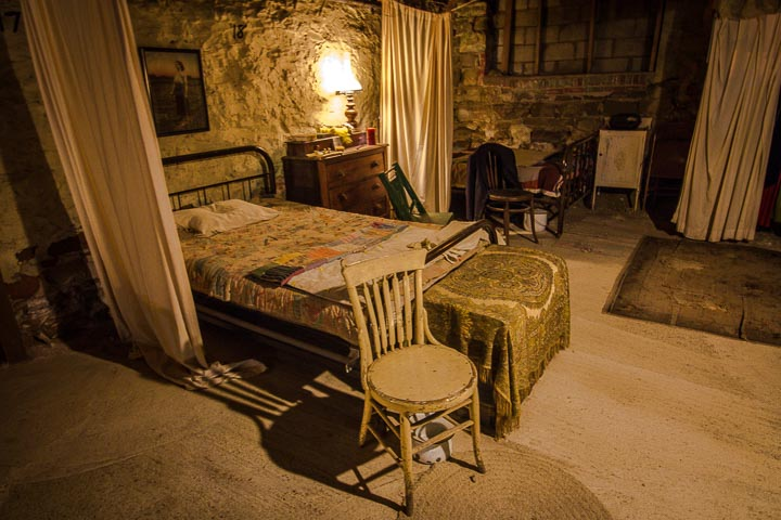 Antique bed, dresser, chairs, rugs, and curtains in a dark room with stone walls