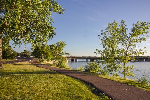 Paved trail between with between a river and a patch of grass, in front of a bridge