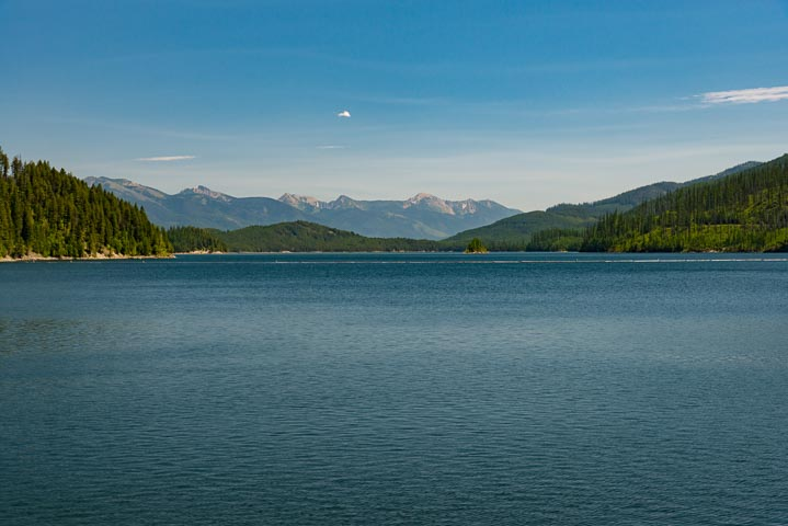 But water with in front of trees and grassy hills, with mountains in the background