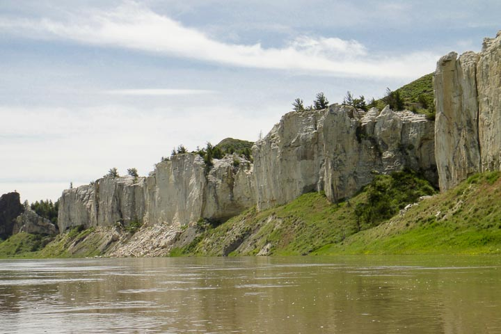 Vertical stone cliffs along a brown body of water