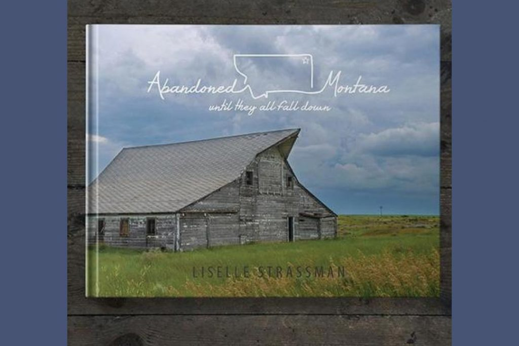 """The booked """"Abandoned Montana: Until They All Fall Down"""" by Liselle Strassman, with an old wooden building on the cover, sitting on a wooden surface."""