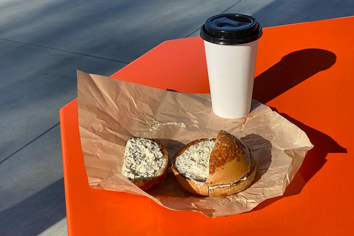 A bagel and paper coffee cup sitting on a brown wrapper on an orange table.