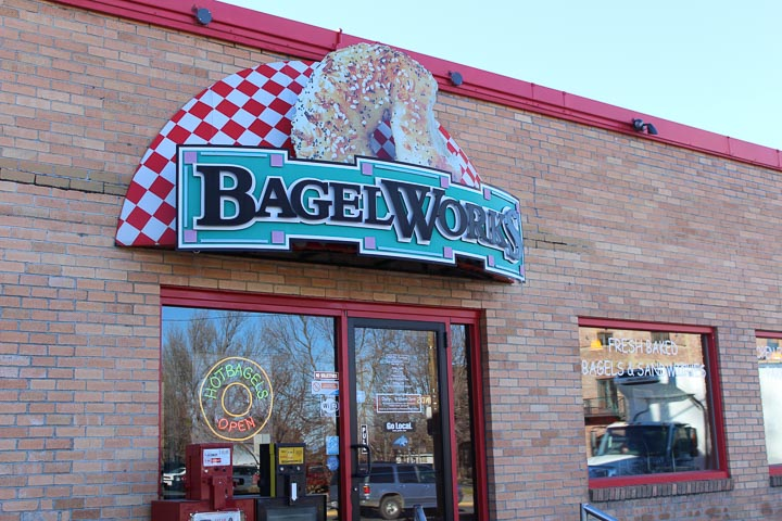 """BagelWorks Bozeman - Exterior of a brick building with an awning reading """"BagelWorks"""" above the entrance."""