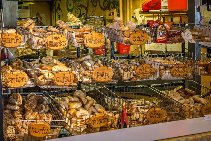 Three rows of bagels in wire baskets, each with a wooden sign listing the flavor.