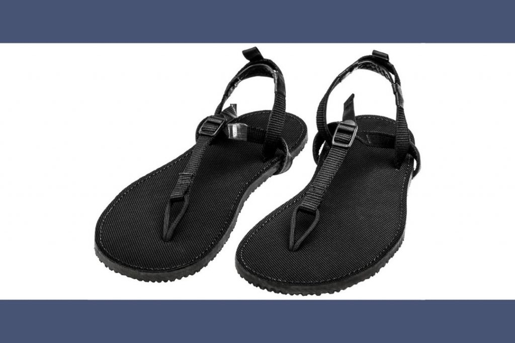 A pair of plain black flip-flops with a heel strap and buckle on the instep.