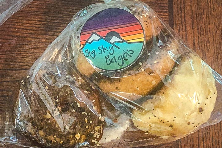 """Plastic bag full of bagels, labeled with a colorful sticker reading """"Big sky Bagels."""""""