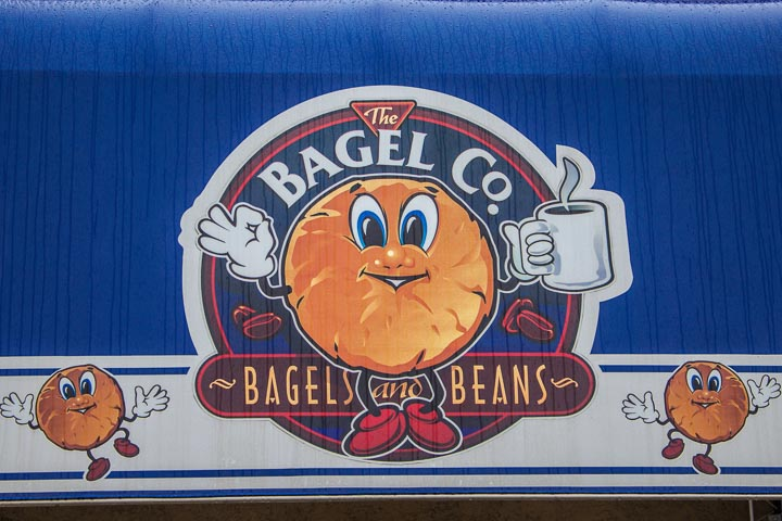 """The Bagel Co. Helena - Painted sign with animated bagels reading """"The Bagel Co. Bagels and Beans"""" on a dark blue background."""
