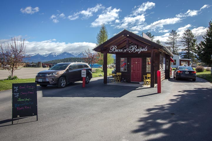 """Small wooden building with a sign reading """"Buzz N Bagels"""" above a red door, with cars pulled up along the side and mountains in the background."""