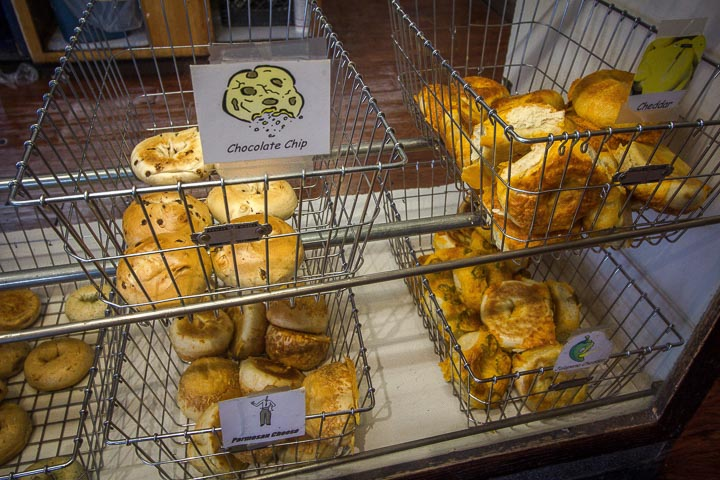 Two shelves of wire baskets full of bagels in wire baskets, each with a white sign stating the flavor.