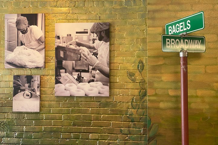 """Indoor decorative street street sign reading """"Bagels"""" and """"Broadway"""" in front fo a brick wall with black-and-white photographs."""