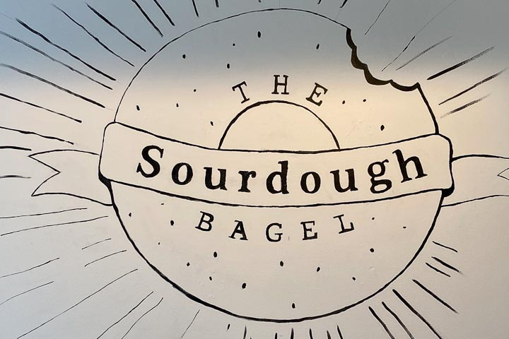 """Simple black-and-white sketch of a bagel with a bite taken out and a banner reading """"The Sourdough Bagel."""""""