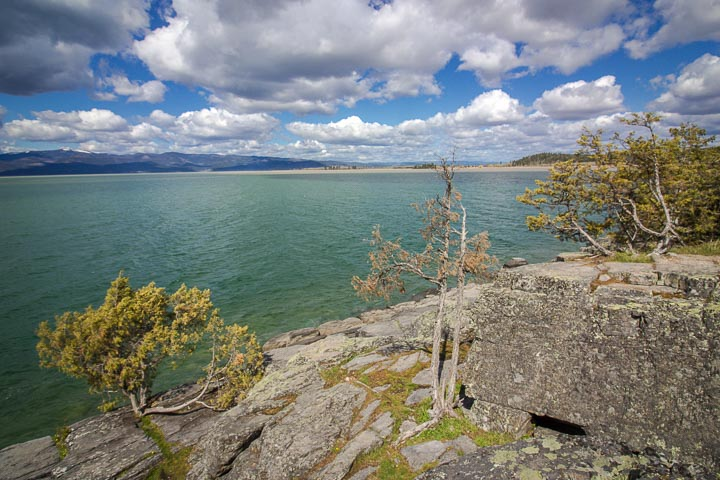 Rocky shore along a blue-green body of water, under a cloudy blue sky.