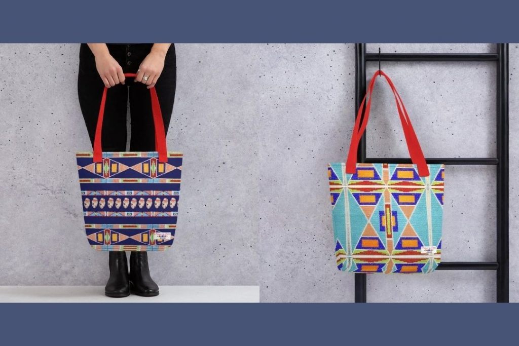 A colorful tote bag in front of a woman's lower body, next to another colorful tote bag hanging from a black ladder.