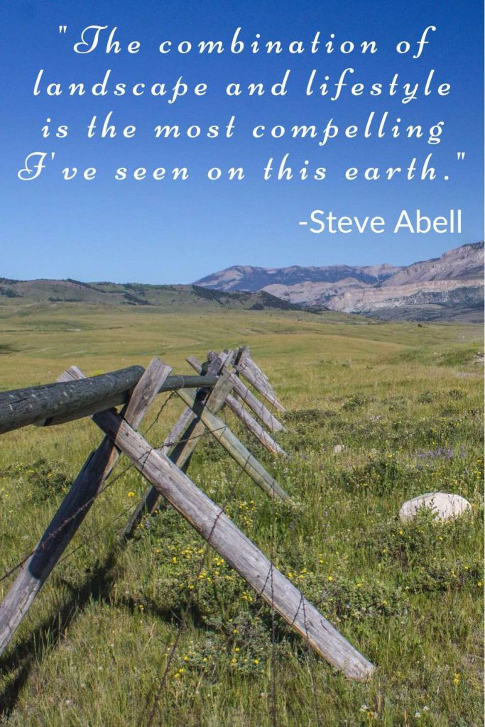Barbed wire fence running through a field in front of bare mountains with Steve Abell quote.