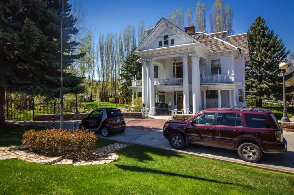 White two story house with large columns at front door and two vehicles parked in circular driveway.