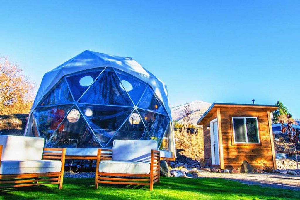 Blue geodesic dome in front of two outdoor chairs and small outhouse.